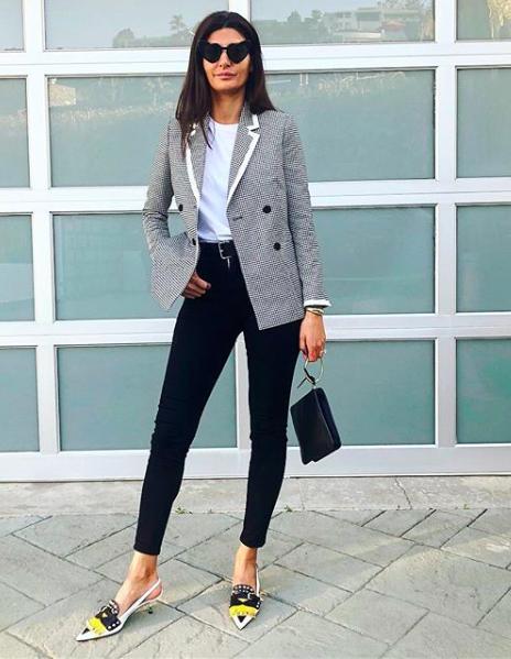 Giovanna Bataglia en un look para los días que no hace ni frío ni calor, con jeans negros, blazer a cuadros, t-shirt blanca, zapatillas, bolsa clutch y lentes oscuros en forma de corazón. Este look con jeans es ideal para los días lluviosos.