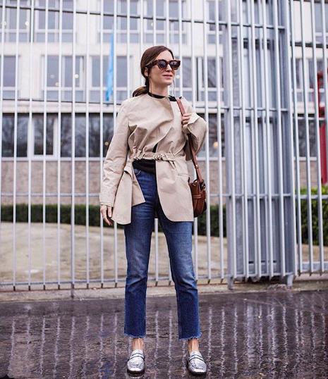Gala Gonzalez en un look de jeans, mocasines plateados, gabardina (trenchcoat) y una bolsa marrón.