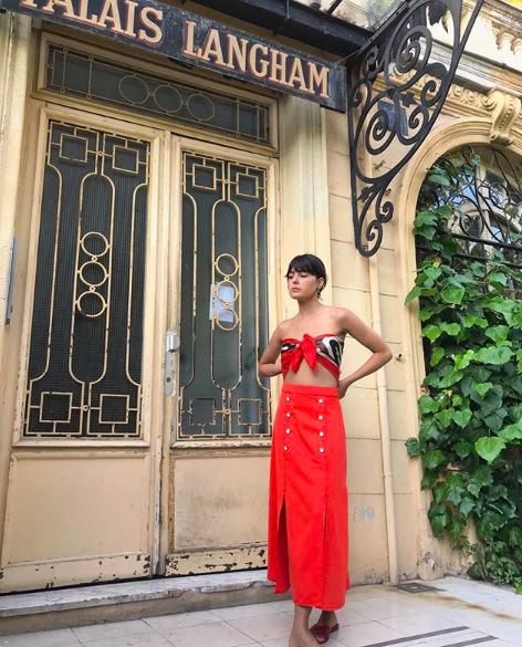 Una falda roja larga, con botones, y una mascada amarrada como si fuera un top es ideal para la época de calor, primavera o verano.