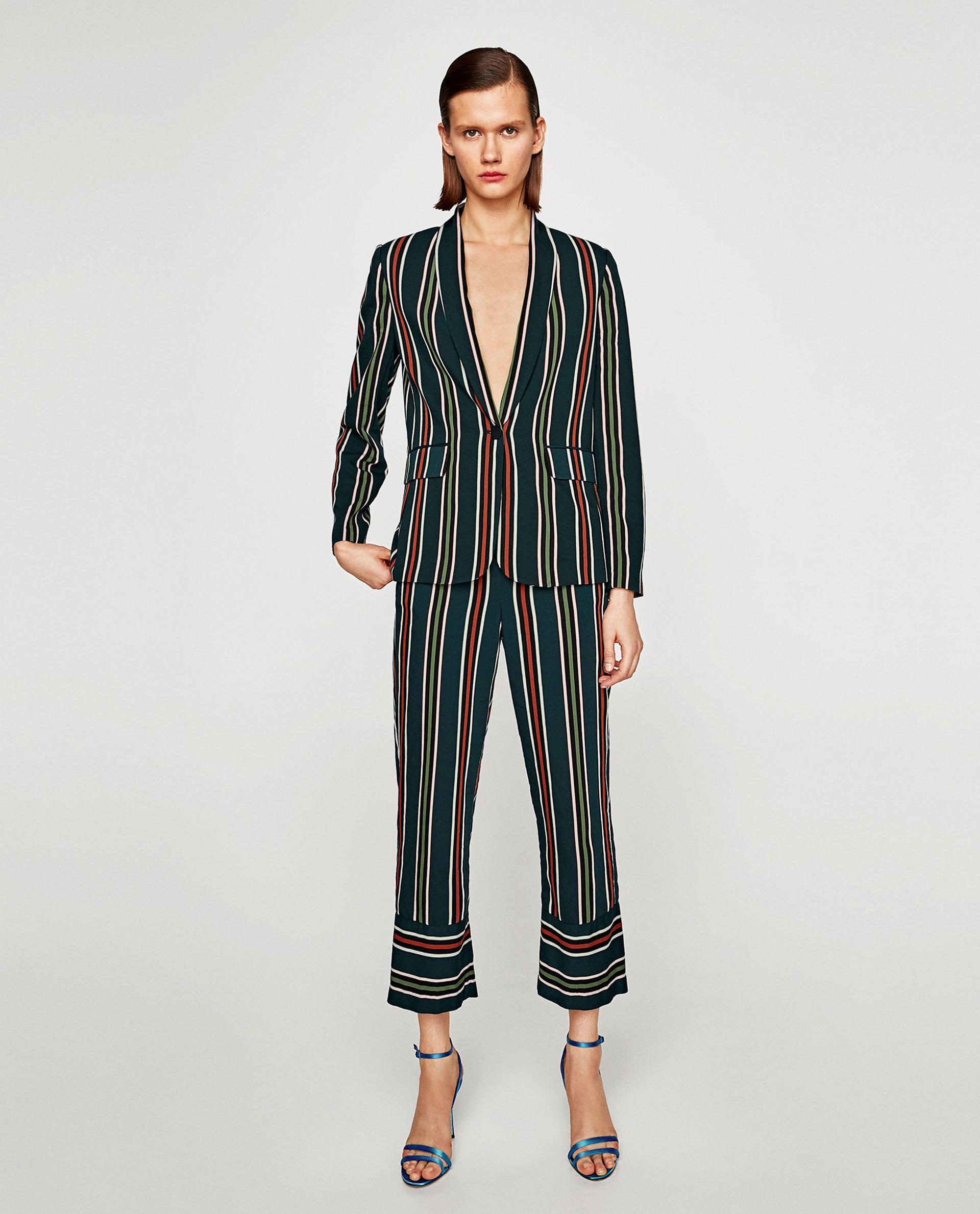pijamaLook pijamero de dos piezas de tela de seda y print de rayas de colores. Los tacones que usa la modelo son de color azul eléctrico.