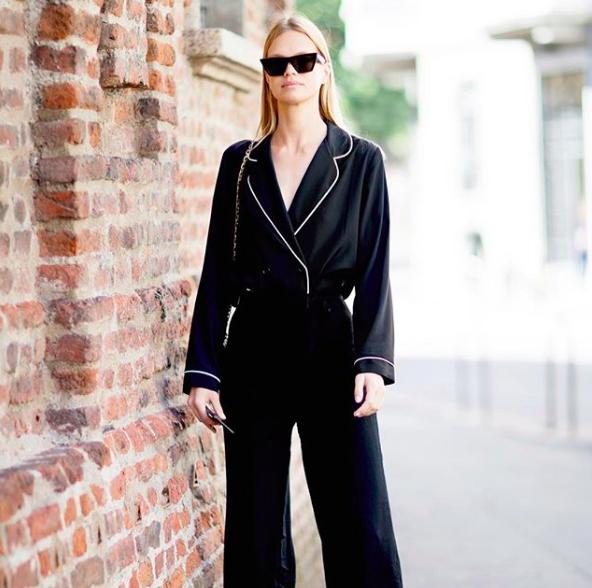 La moda pijamera se ve en este look de dos piezas liso y de color negro, el outfit combina con los lentes de sol negros y maquillaje y peinado natural.