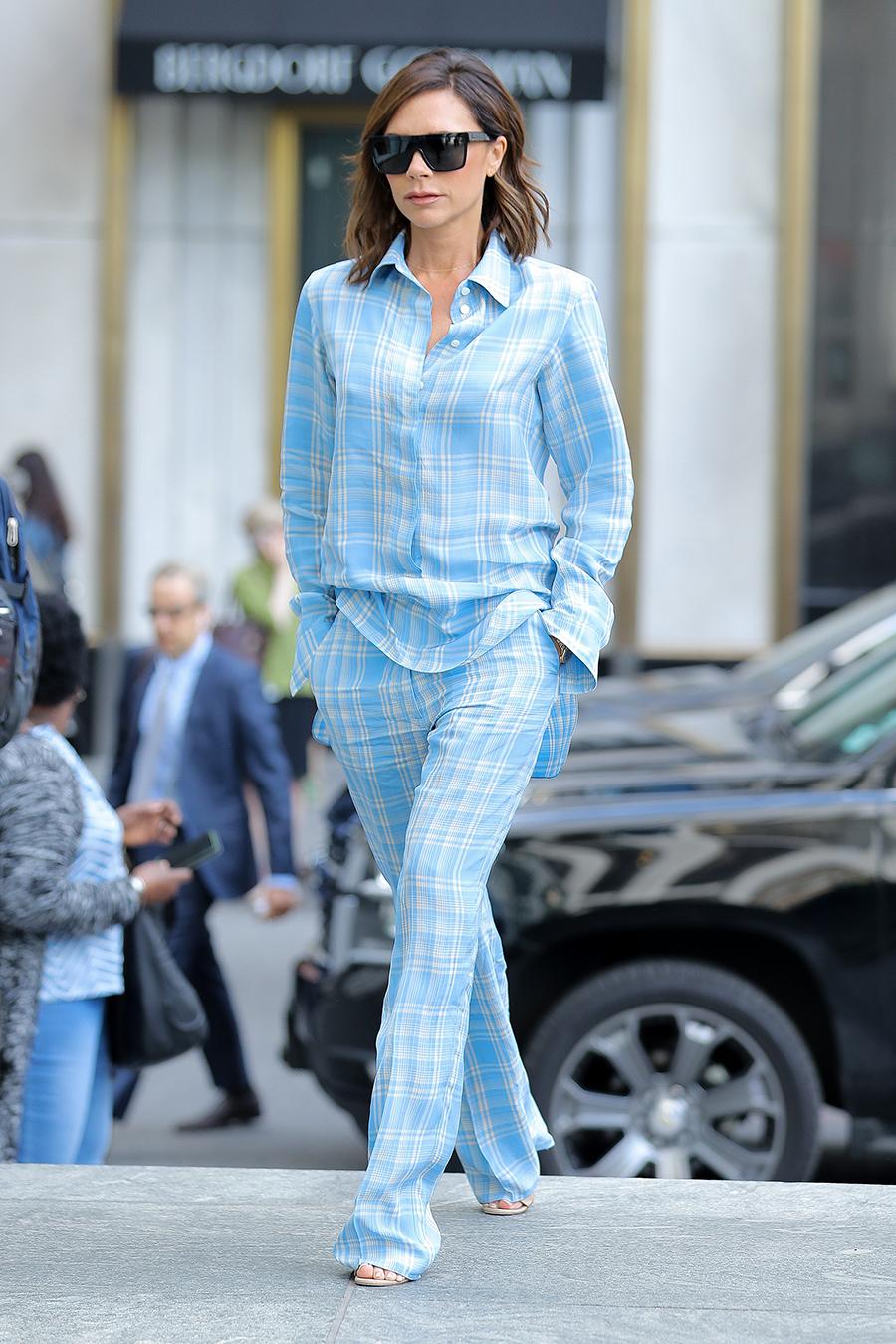 Victoria Beckham se atreve a usar un look pijamero de dos piezas azul con cuadros y tela de franela. Su peinado es natural corto y viste unos lentes de sol que la hacen lucir chic.