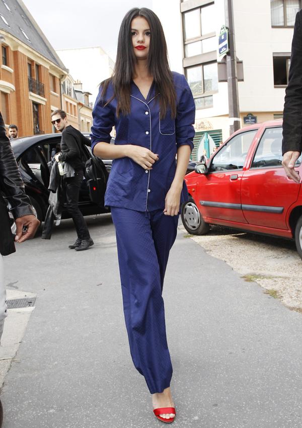 Selena Gomez luce un look pijamero de dos piezas azul marino lizo. Su peinado es pelo suelto natural y despeinado hace juego con su boca roja.