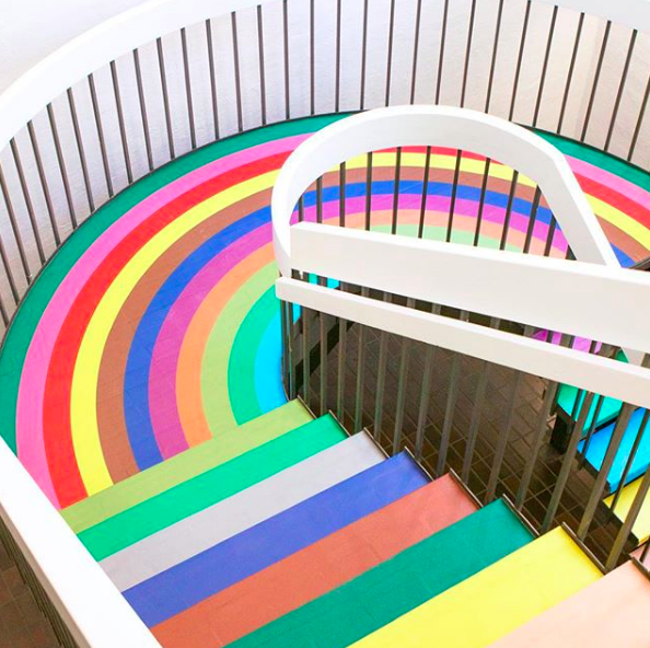 Escalera decorada de colore que hace parecer que hay un arcoiris dentro de la casa