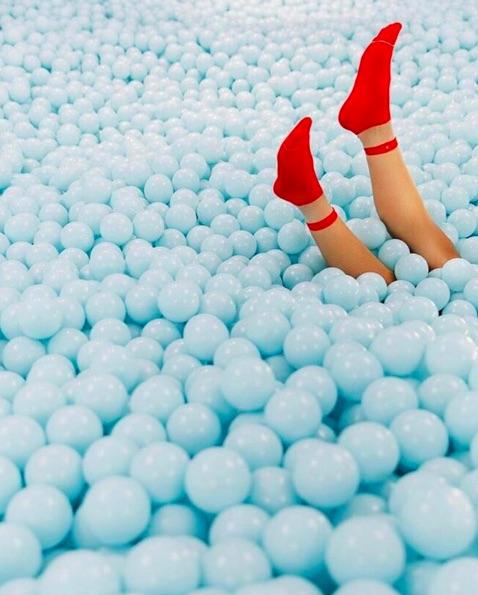 Alberca de pelotas azules para que jueguen niños y adultos en la exposición de Color Factory.